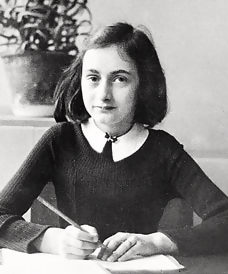 Photo of Anne Frank sitting at a writing desk