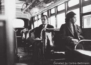 Photograph of Rosa Parks sitting on a bus with a white man behind her